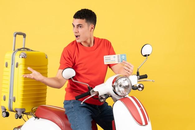 Вид спереди молодой человек на мопеде с желтым чемоданом с билетом
