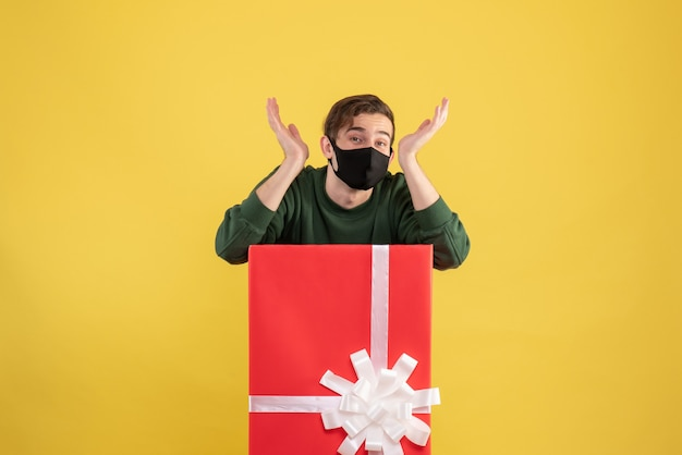 Front view young man opening hands standing behind big giftbox on yellow