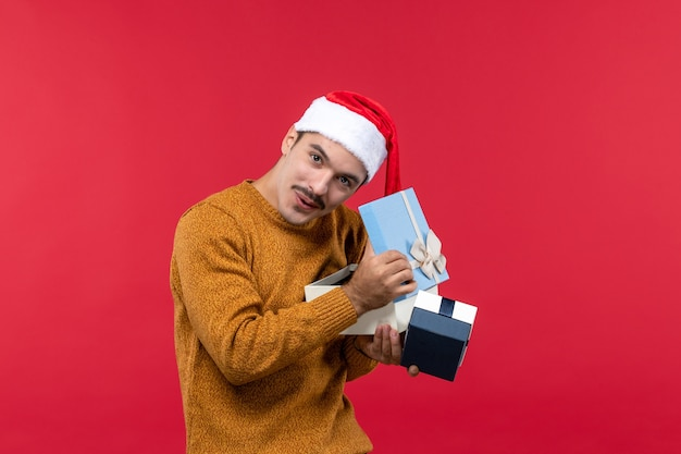 Front view of young man opening presents on a red wall