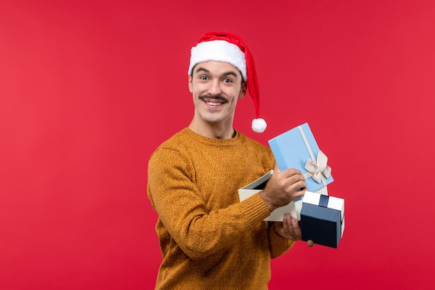 Front view of young man opening presents on red wall