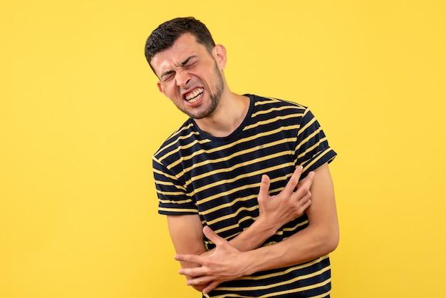 Vista frontale giovane uomo nel dolore in piedi su sfondo giallo isolato