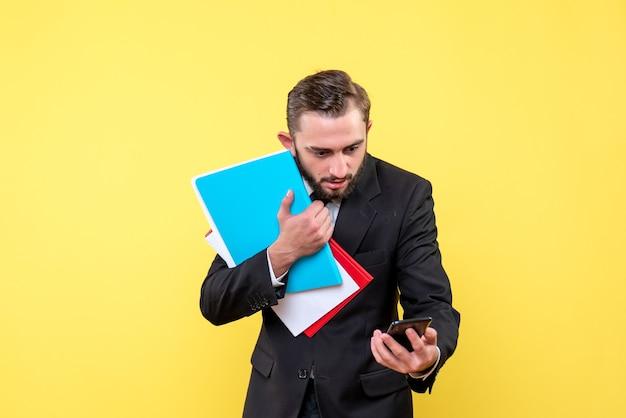 Vista frontale del giovane uomo perplesso giovane imprenditore tenendo le cartelle e un telefono in giallo