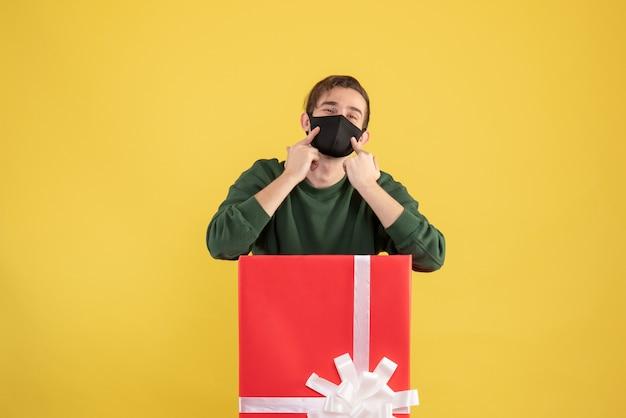 노란색에 큰 giftbox 뒤에 서있는 마스크에서 가리키는 전면보기 젊은 남자