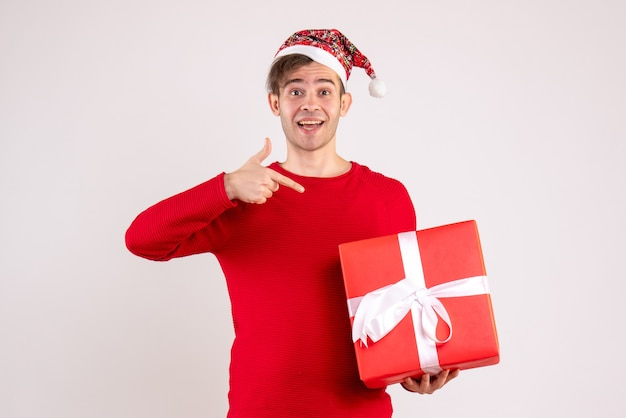 Front view young man pointing at gift standing on white
