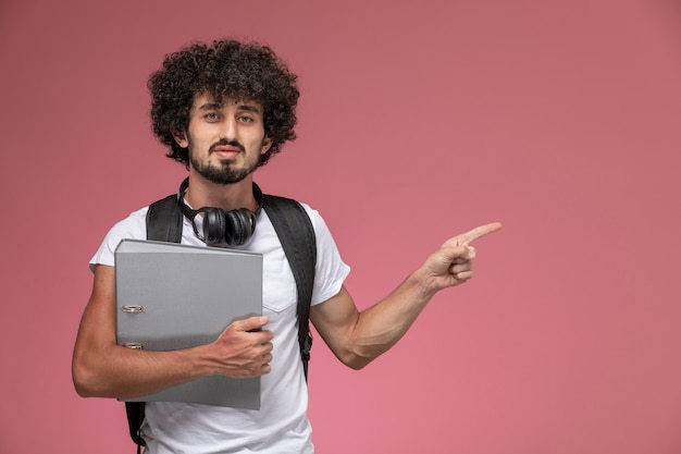 Front view young man pointing out his left direction with binder and headphone