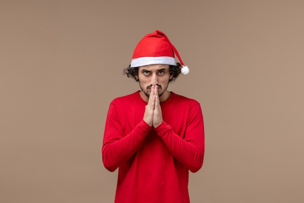 Front view young man praying on brown desk holiday emotion christmas