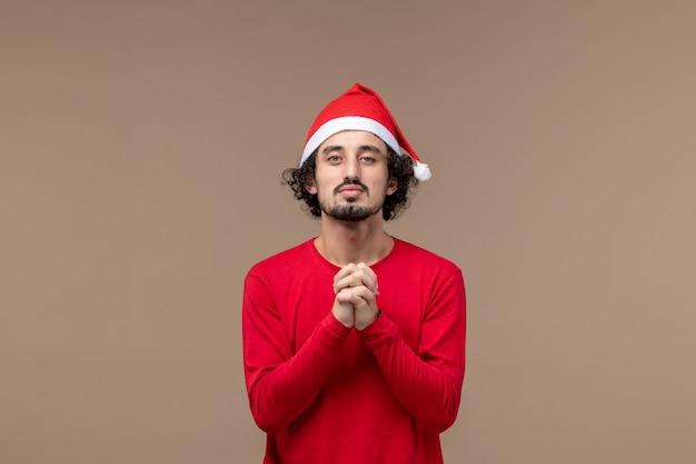 Вид спереди молодой человек молится на коричневом фоне праздничные эмоции рождество