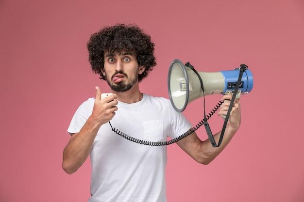 Вид спереди молодой человек, вытаскивая язык и держа в руке микрофон