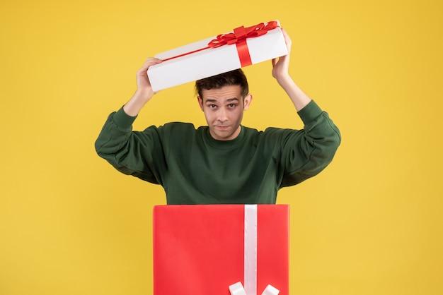 Giovane di vista frontale che mette la copertura sopra la sua testa che sta dietro il grande giftbox su giallo