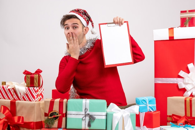크리스마스 선물 주위에 앉아 그의 입에 손을 넣어 전면보기 젊은 남자