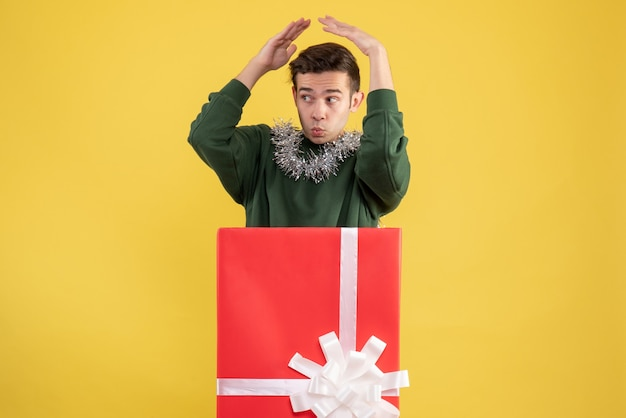 Front view young man putting hands over his head standing behind big giftbox on yellow