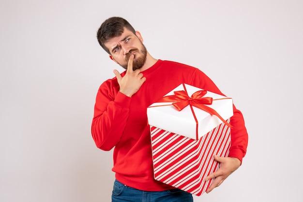 Vista frontale del giovane in camicia rossa che tiene regalo di natale in scatola pensando sul muro bianco