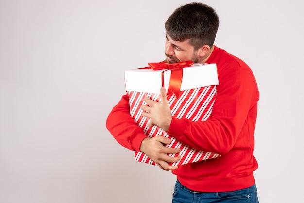 Vista frontale del giovane in camicia rossa che tiene regalo di natale nella casella sul muro bianco