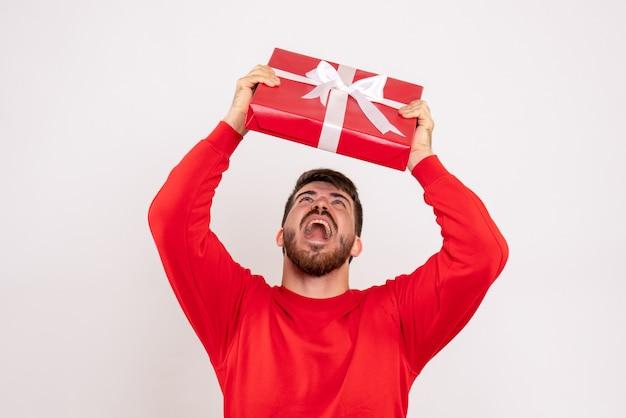 Vista frontale del giovane in camicia rossa che tiene regalo di natale sulla parete bianca