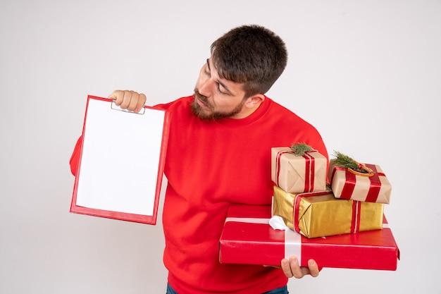 Vista frontale del giovane in camicia rossa che tiene i regali di natale e la nota di archivio sul muro bianco