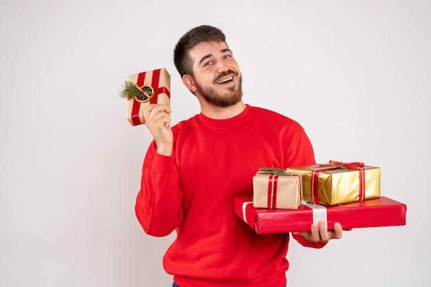 Vista frontale del giovane in camicia rossa che tiene i regali di natale sulla parete bianca
