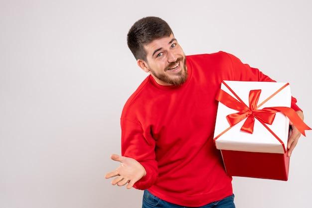 Vista frontale del giovane in camicia rossa che tiene il natale presente nella casella sulla parete bianca