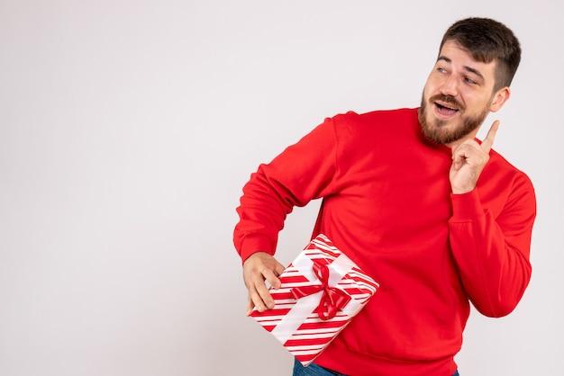 Vista frontale del giovane in camicia rossa che tiene presente di natale sulla parete bianca