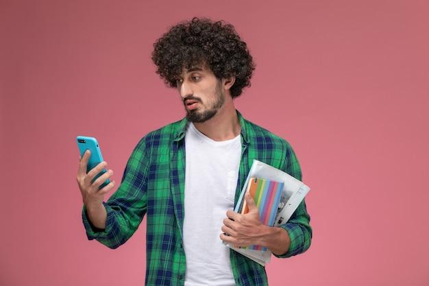 正面図若い男は電話で奇妙なニュースを見る