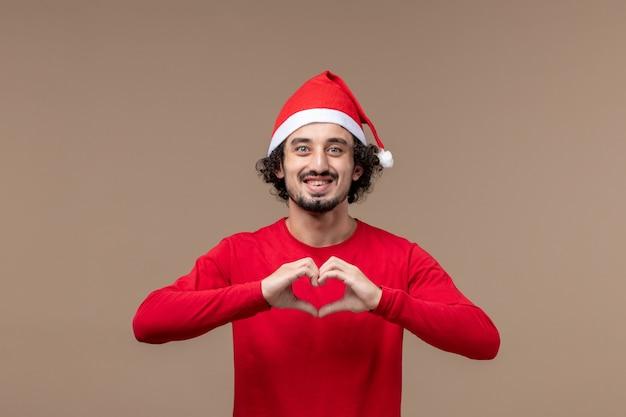 Вид спереди молодой человек, отправляющий любовь на коричневом фоне, праздничные эмоции, рождество