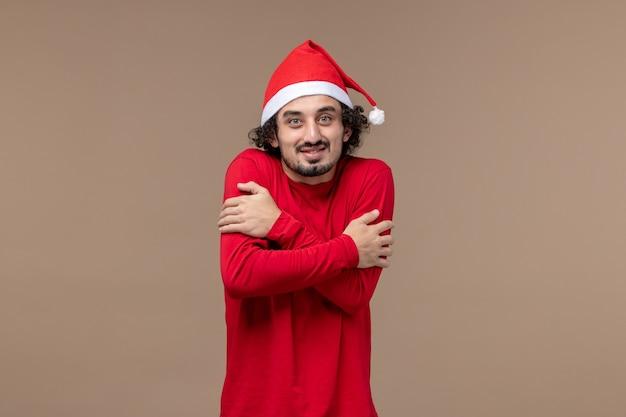 Вид спереди молодого человека, дрожащего от холода на коричневом фоне, рождественские эмоции, праздник
