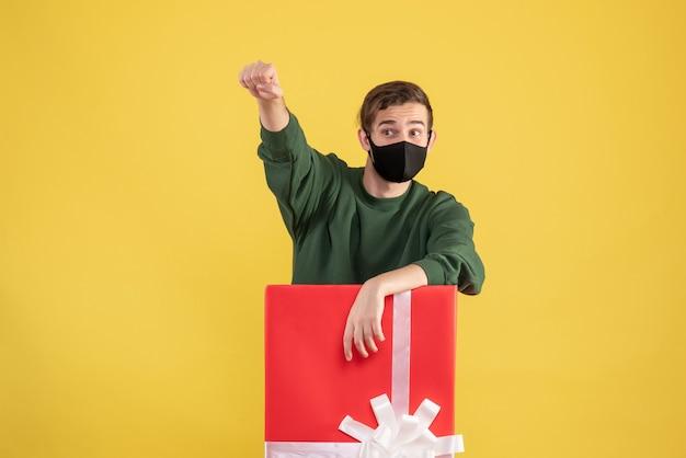 黄色の大きなギフトボックスの後ろに立っているスーパーヒーローのジェスチャーを示す正面図の若い男
