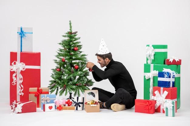 Vista frontale del giovane che si siede intorno ai regali di festa che decorano il piccolo albero sulla parete bianca