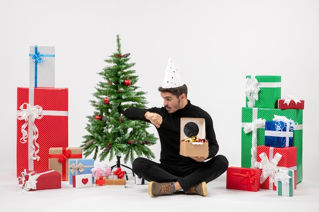 Front view of young man sitting around holiday presents holding tree toys checking time on white wall