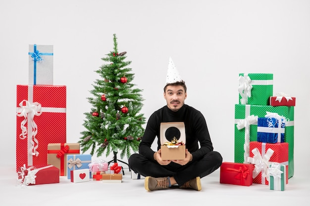 Front view of young man sitting around holiday presents holding tree toys on a white wall