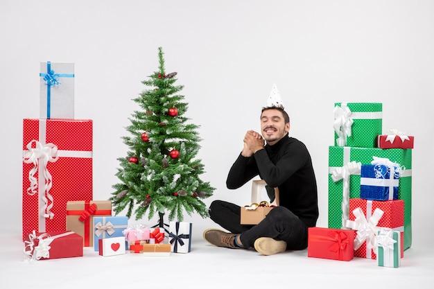 Vista frontale del giovane uomo seduto intorno ai regali di festa sul muro bianco