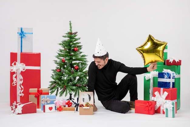 Vista frontale del giovane uomo seduto intorno a regali e tenendo la figura della stella d'oro e ridendo sul muro bianco