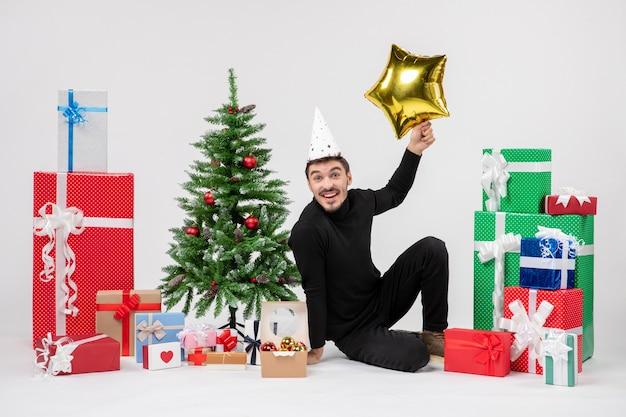 Vista frontale del giovane che si siede intorno ai regali e che tiene la figura della stella d'oro sul muro bianco