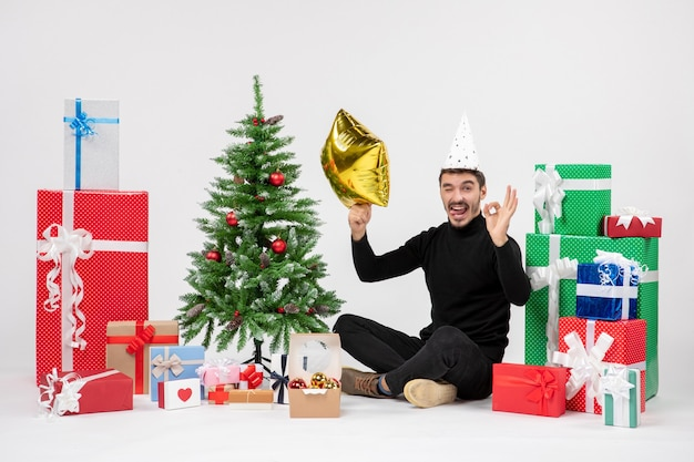 Front view of young man sitting around presents and holding gold star figure on white wall
