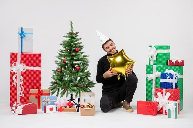 Vista frontale del giovane uomo seduto intorno a regali e tenendo palloncino a forma di stella d'oro sul muro bianco