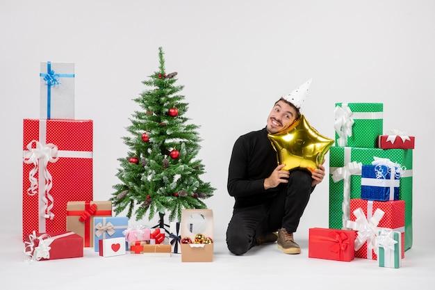 Vista frontale del giovane che si siede intorno ai regali e che tiene il cuscino a forma di stella d'oro sorridente sul muro bianco