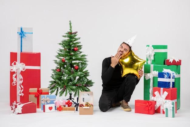 Vista frontale del giovane che si siede intorno ai regali e che tiene il cuscino a forma di stella d'oro sul muro bianco