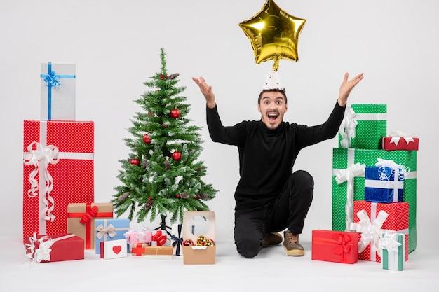 Vista frontale del giovane uomo seduto intorno a regali e gettando la figura della stella d'oro sul muro bianco