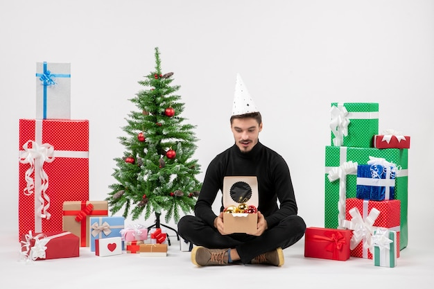 Front view of young man sitting around presents on white wall
