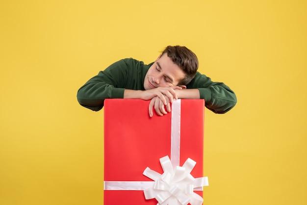 Вид спереди молодой человек спит за большой подарочной коробкой, положив голову на коробку на желтом