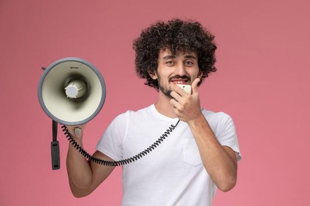 Вид спереди молодой человек улыбается и сообщает с ручным микрофоном