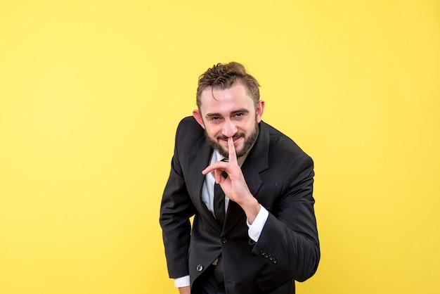 Vista frontale del giovane uomo d'affari sorridente che punta il dito alla bocca su giallo
