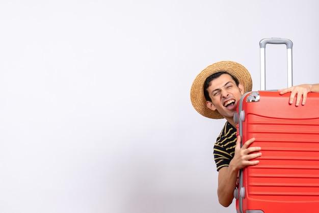 Вид спереди молодой человек, стоящий за красным чемоданом, держа шляпу