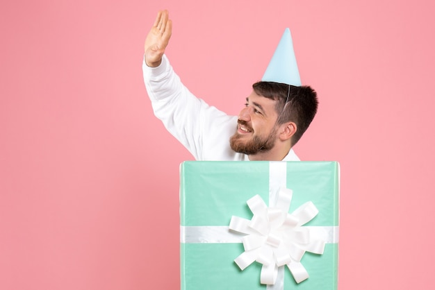 Front view of young man standing inside present box and greeting on pink wall