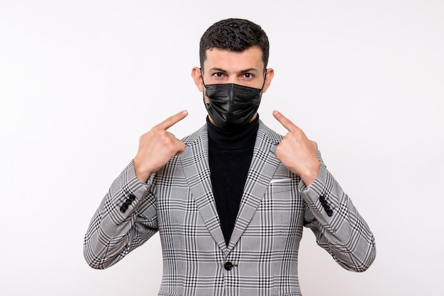 Front view young man in suit pointing at mask standing on white isolated background