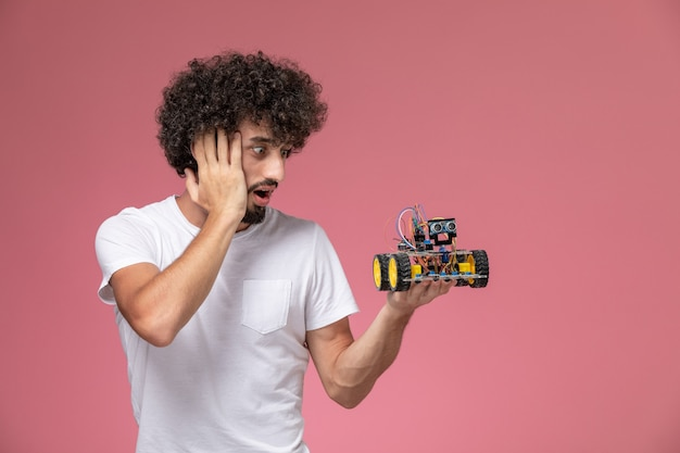 Front view young man surprising by his robotic innovation