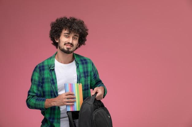正面図若い男は彼のバッグから彼のノートを取り出します