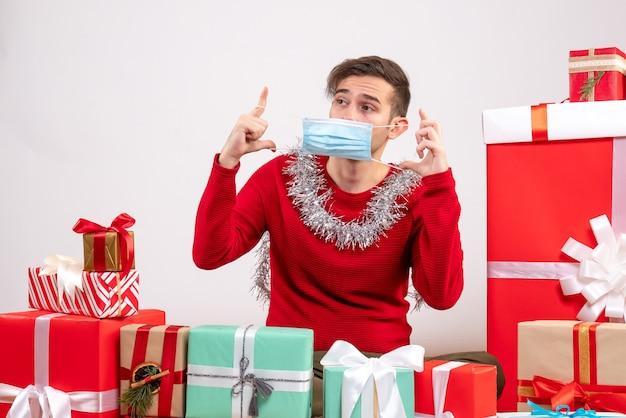 Giovane di vista frontale che toglie la sua maschera che si siede intorno ai regali di natale