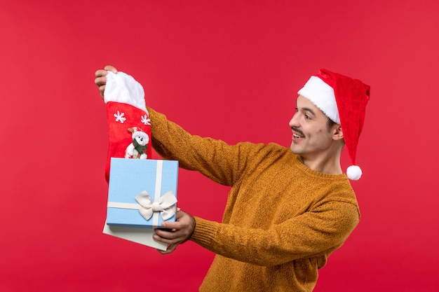 Front view of young man taking out christmas sock on a red wall