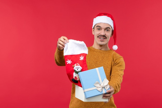 Front view of young man taking out christmas sock on red wall