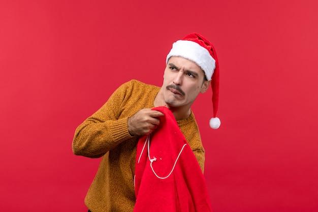 Vista frontale del giovane che prende i regali dalla borsa sulla parete rossa